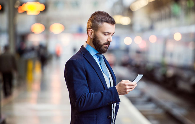 Man standing on train platform with his phone