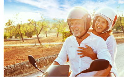 Two people on a motorbike in the countryside